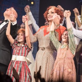 Alex Bourne (Daddy Warbucks), Ruby Stokes (Annie) Craig Revel Horwood (Miss Hannigan), Nancy Allsop (July), Jonny Fines (Rooster) - Annie at the Piccadilly Theatre - Photo credit Craig Sugden